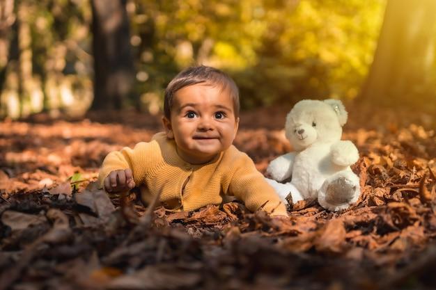 Niño con un oso de peluche blanco en el parque en una puesta de sol de otoño. iluminación natural, bebé de mediados de año acostado sobre las hojas de los árboles