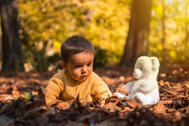 Niño con un oso de peluche blanco en el parque en un soleado día de otoño. iluminación natural, bebé de mediados de año acostado sobre las hojas de los árboles