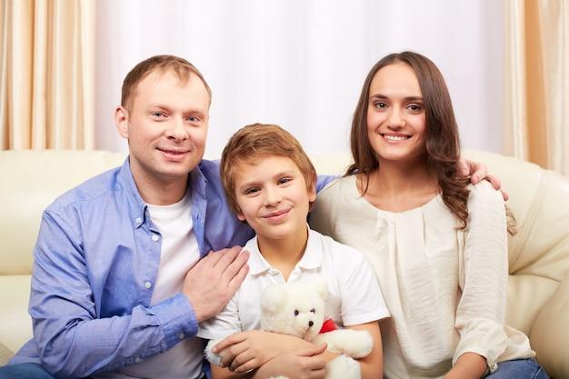 Niño con oso de peluche y sus padres