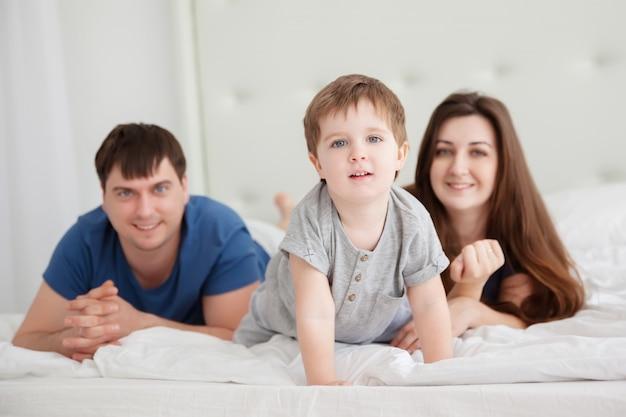 Niño y padres en la cama de los padres vistiendo pijamas