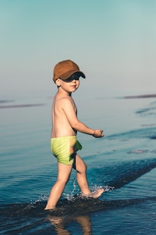 Un niño con pantalones cortos verdes y una gorra de béisbol marrón camina sobre el mar cerca de la orilla espacio de copia