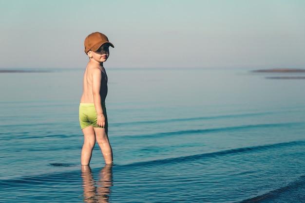 Niño en pantalones cortos verdes y gorra de béisbol marrón se encuentra en el mar. copie el espacio. foto de minimalismo entonado.