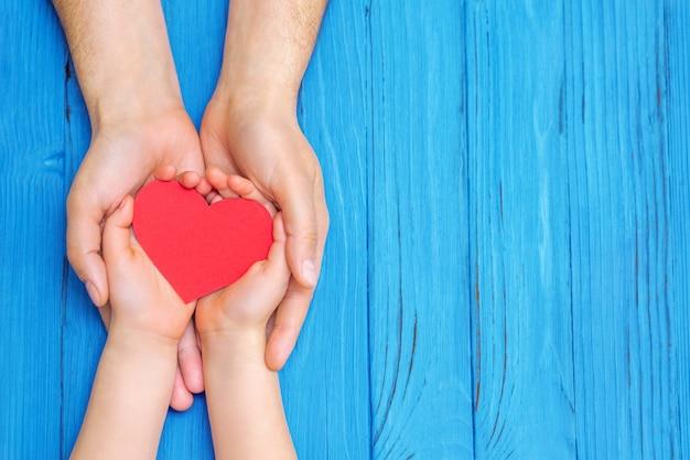 Niño y papá manos sosteniendo corazón rojo.
