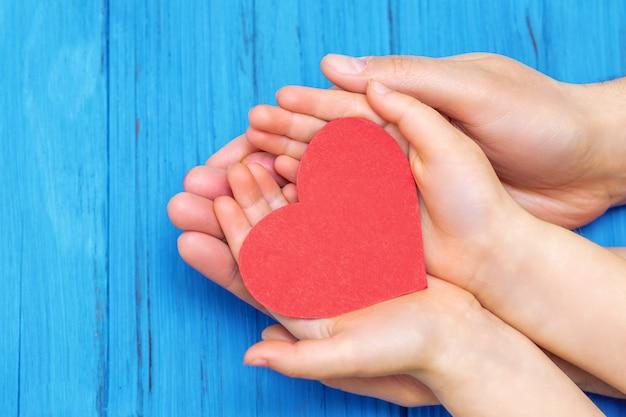 Niño y papá manos sosteniendo corazón rojo