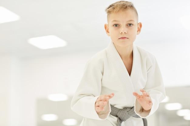 El niño parado en una posición de lucha