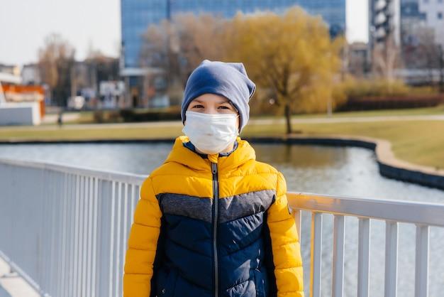 Un niño está parado sobre un fondo gris con una máscara durante una cuarentena con espacio libre. cuarentena en la máscara.