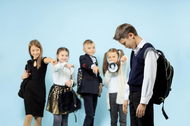 Niño parado solo y sufriendo un acto de acoso mientras los niños se burlan en la pared