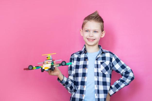 Niño en una pared rosa juega avión robot