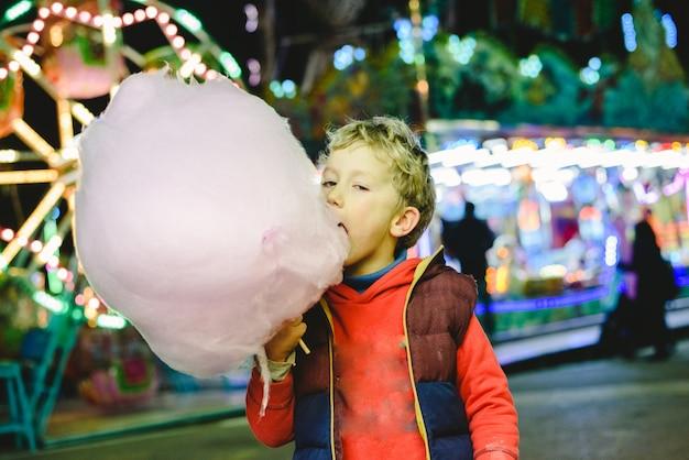 Niño pasando un buen rato comiendo un algodón de azúcar en una feria nocturna.