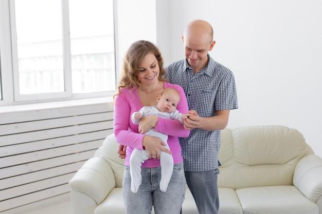 Niño, paternidad, concepto de personas bebé en manos de los padres en una pared blanca.