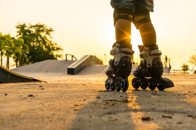 El niño patinando en el parque público con equipos de protección en el fondo del atardecer