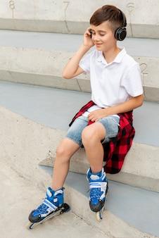 Niño con patines en línea y auriculares