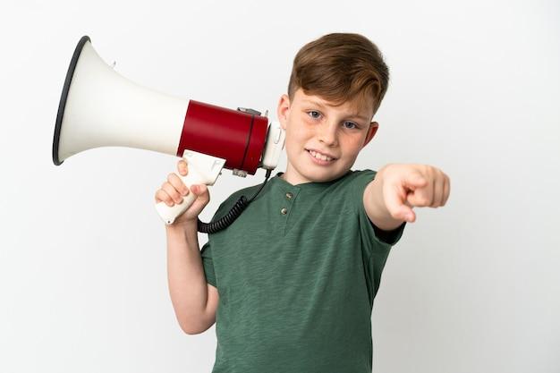 Niño pelirrojo aislado en la pared blanca sosteniendo un megáfono y sonriendo mientras apunta hacia el frente