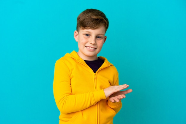 Niño pelirrojo aislado sobre fondo azul aplaudiendo