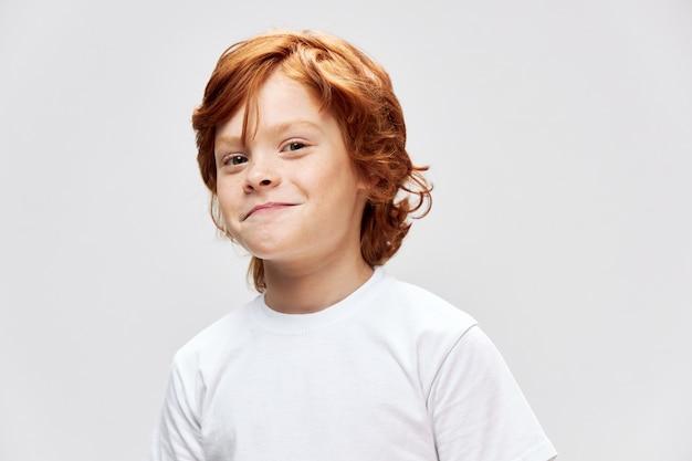 Niño pelirrojo alegre en una camiseta blanca