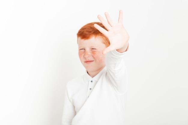 Niño pelirrojo estirando la mano