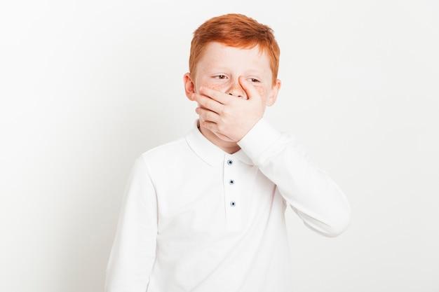 Niño pelirrojo con expresión aburrida
