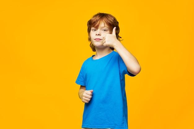 Niño pelirrojo feliz en una camiseta amarilla que muestra el pulgar hacia arriba aislado