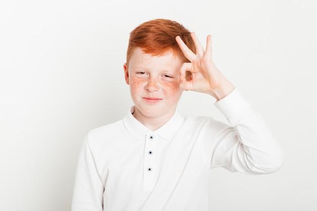 Niño pelirrojo haciendo gesto de mano