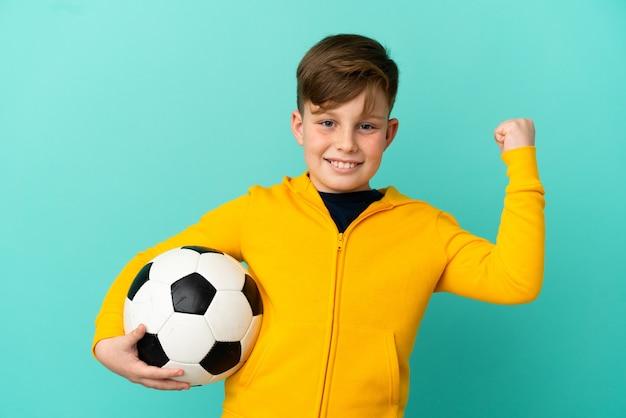 Niño pelirrojo jugando al fútbol aislado sobre fondo azul celebrando una victoria