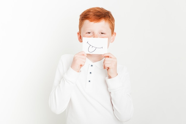 Niño pelirrojo sujetando tarjeta enfrente de cara