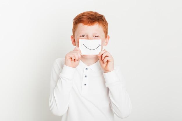 Niño pelirrojo con tarjeta de boca sonriente