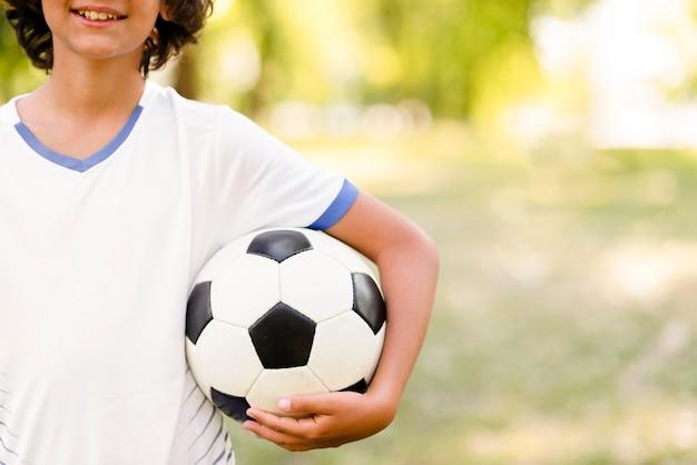 Niño con pelo largo sosteniendo una pelota de fútbol con espacio de copia