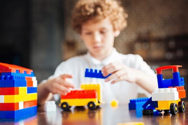 Niño de pelo rizado sentado en una mesa y concentrándose en una nueva obra maestra de plástico en el fondo.