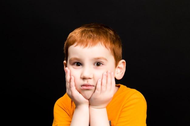 Un niño con el pelo rojo tiene las manos sobre la cara, un niño con una cara hermosa contra un oscuro