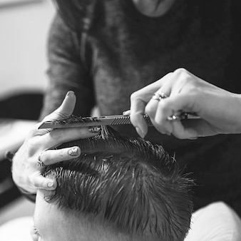 Niño en la peluquería. el niño tiene miedo de los cortes de pelo. manos de peluquero haciendo peinado a niño, de cerca. corte de pelo de moda para niños.