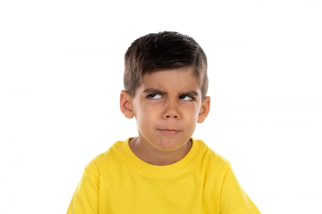 Niño pensativo con camiseta amarilla.
