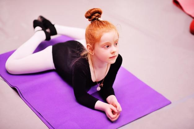 Niño - la pequeña bailarina pelirroja linda realiza ejercicios de estiramiento en la escuela de ballet