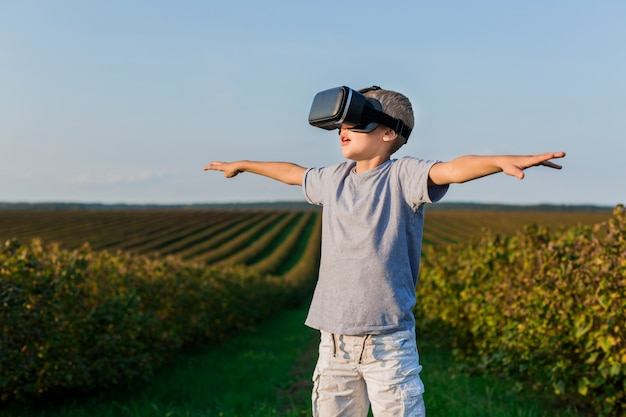 Niño pequeño adorable divirtiéndose con gafas de realidad virtual
