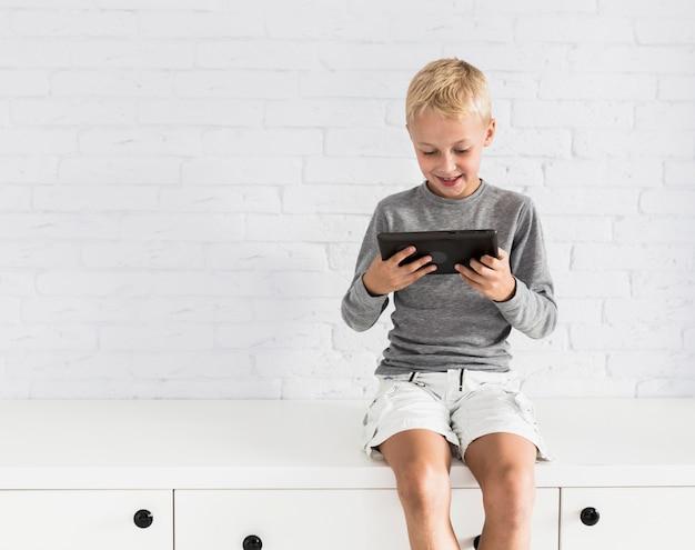 Niño pequeño adorable divirtiéndose con tablet