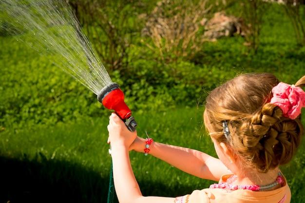 Niño pequeño, adorable niña pequeña, regando las plantas, césped verde