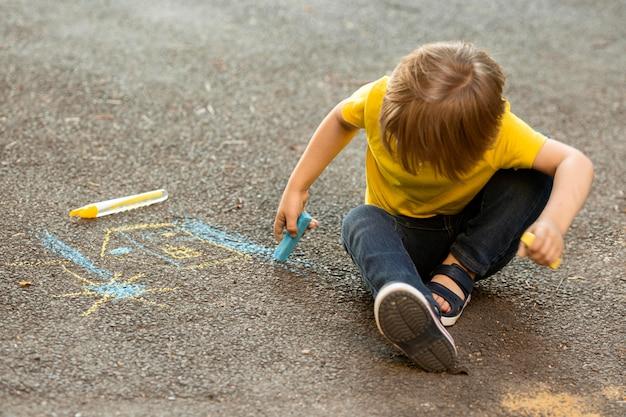 Niño pequeño de alto ángulo en el dibujo del parque