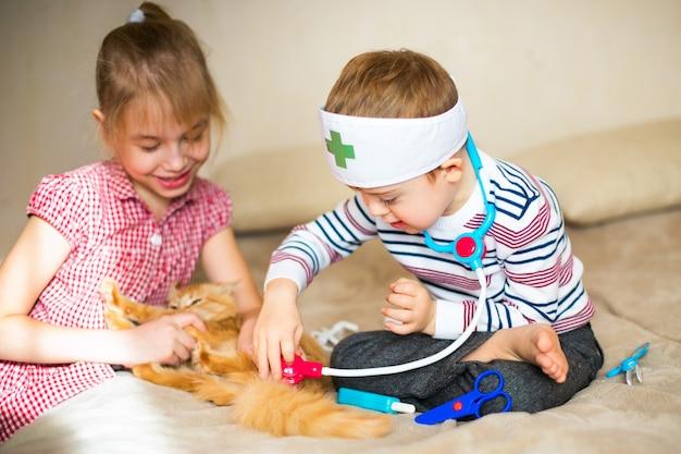 Niño pequeño en los anteojos con síndrome amanecer y niña rubia juega con juguetes y gato jengibre