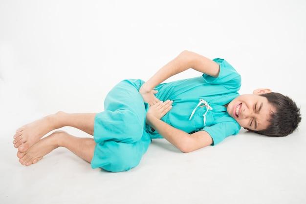 El niño pequeño asianteenager tiene dolor de estómago
