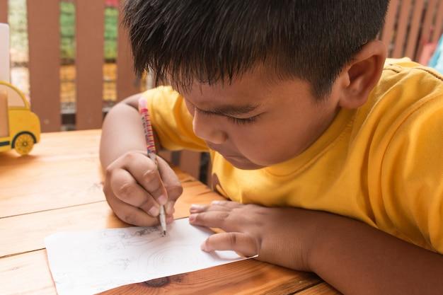 Niño pequeño asiático del niño lindo que hace la preparación en la tabla