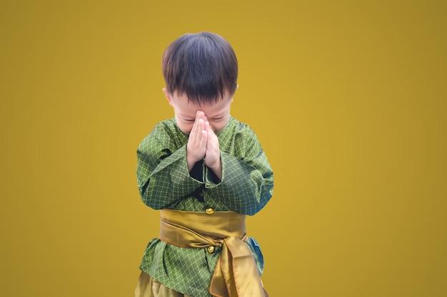 Niño pequeño asiático en traje vintage tailandés