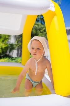 Un niño pequeño en bañador y un sombrero de panamá se está bañando en una piscina inflable