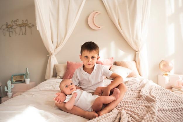 Niño pequeño con bebé recién nacido