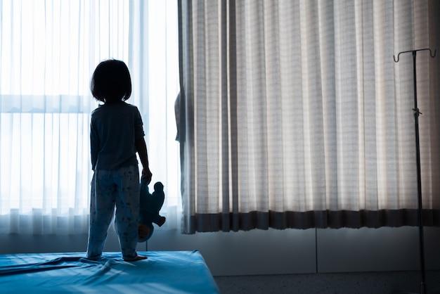 Niño pequeño bebé sentado en la cama jugando con la muñeca en el cuarto oscuro