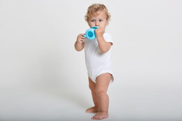 Niño pequeño bebiendo agua de un biberón azul, niño vestido con un traje blanco, mirando a otro lado, de pie descalzo contra la pared ligera, encantador niño pequeño siente sed.