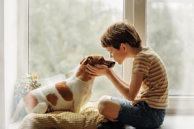 El niño pequeño besa al perro en nariz en la ventana.