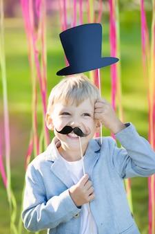 Niño pequeño con bigote de papel divertido y sombrero en fiesta de cumpleaños
