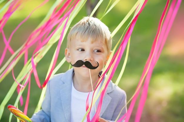 Niño pequeño con bigote de papel divertido