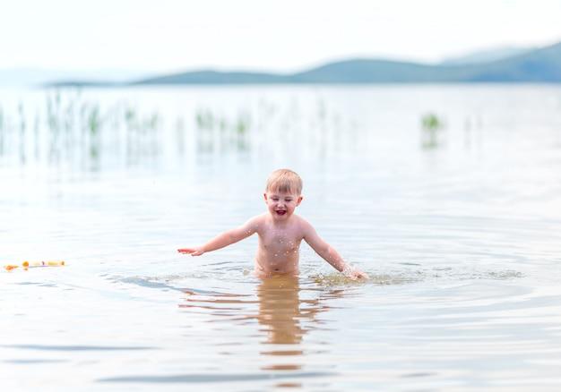 Un niño pequeño con cabello rubio se divierte en el mar nadando, verano, endureciendo
