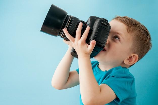 Niño pequeño con cámara sobre un fondo azul
