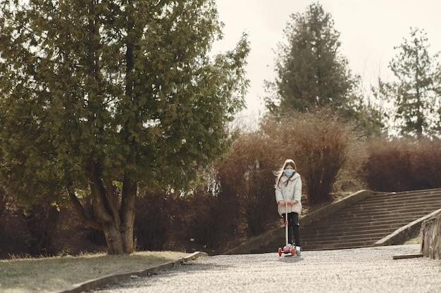 Niño pequeño camina afuera en una máscara